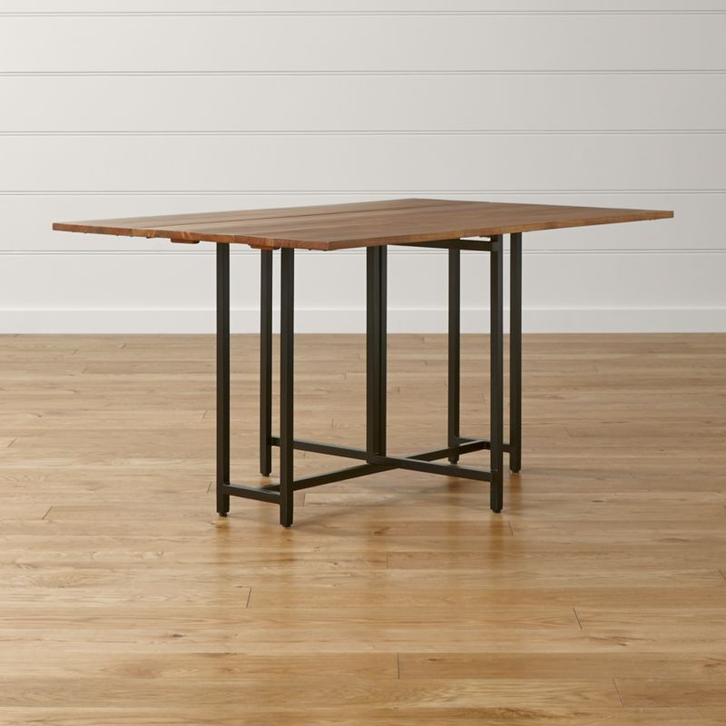 The Origami drop leaf dining table unfolds its updated look in black metal and beautifully grained acacia wood, bleached and stained light walnut. <NEWTAG/><ul><li>Solid, bleached acacia wood</li><li>Light walnut finish and clear lacquer topcoat</li><li>Tubular steel legs with black powdercoat finish</li><li>Butt-joint laminated top</li><li>Plastic leveling feet</li><li>Seats four</li><li>Made in India</li></ul><br />
