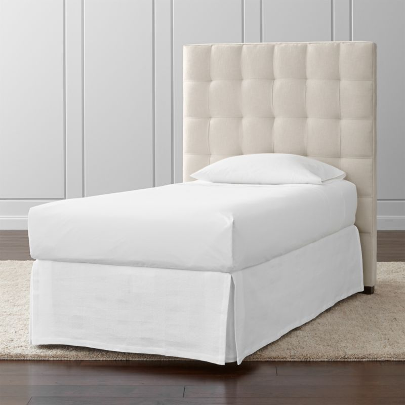 "The twin size of our Quadrant headboard lines up on the grid as a tall presence for the contemporary bedroom. Each twin headboard is wrapped in a soft, cotton-poly blend fabric, with buttonless tufting adding casual definition and visual interest. The Quadrant Twin Headboard is a Crate and Barrel exclusive.<br /><br /><NEWTAG/><ul><li>Frame is benchmade with certified sustainable hardwood that's kiln-dried to prevent warping</li><li>Soy-based polyfoam cushioning</li><li>Solid maple legs with brown finish</li><li>Headboard requires a bed frame (sold separately)</li><li>When attached to Crate and Barrel bed frame no additional hardware required; -Accommodates <a href=""/furniture/mattresses-foundations/1"">mattress and box spring</a> (sold separately)</li><li>Non-Crate and Barrel bed frame may require a Modi-Plate Kit (sold separately)</li><li>Made in North Carolina, USA</li></ul><br />"