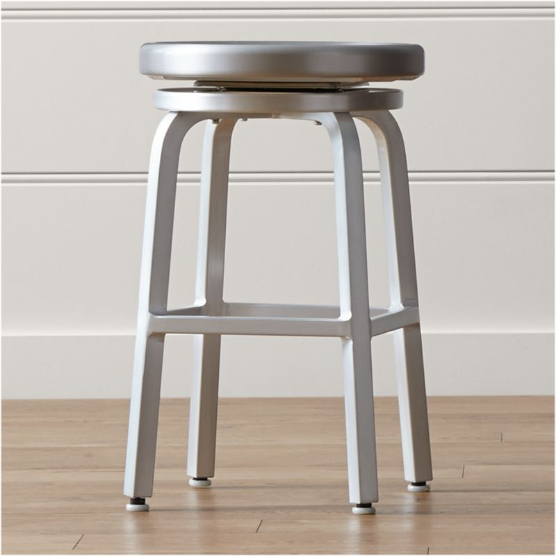This contemporary brushed aluminum counter stool pulls up to the kitchen counter with the classic 360-degree spin, with ball bearing action for a smooth ride. <NEWTAG/><ul><li>Traditional base design with foot rungs</li><li>Foot caps to protect floor surfaces</li><li>Clear lacquer finish</li><li>Caution:  Do not place fingers or hands beneath stool seat as there are moving parts and edges may be sharp.</li><li>Made in China</li></ul>