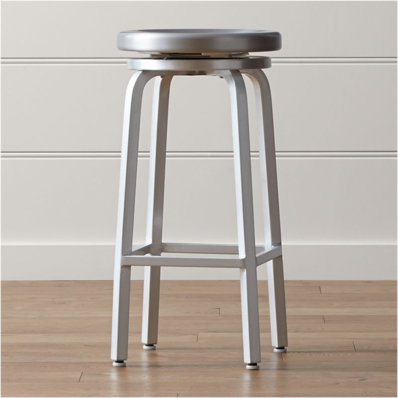 This industrial, contemporary brushed aluminum bar stool has a bar-appropriate height and offers the classic 360-degree spin, with ball bearing action for a smooth ride. <NEWTAG/><ul><li>Traditional base design with foot rungs</li><li>Foot caps to protect floor surfaces</li><li>Clear lacquer finish</li><li>Caution:  Do not place fingers or hands beneath stool seat as there are moving parts and edges may be sharp.</li><li>Made in China</li></ul><br /><br />