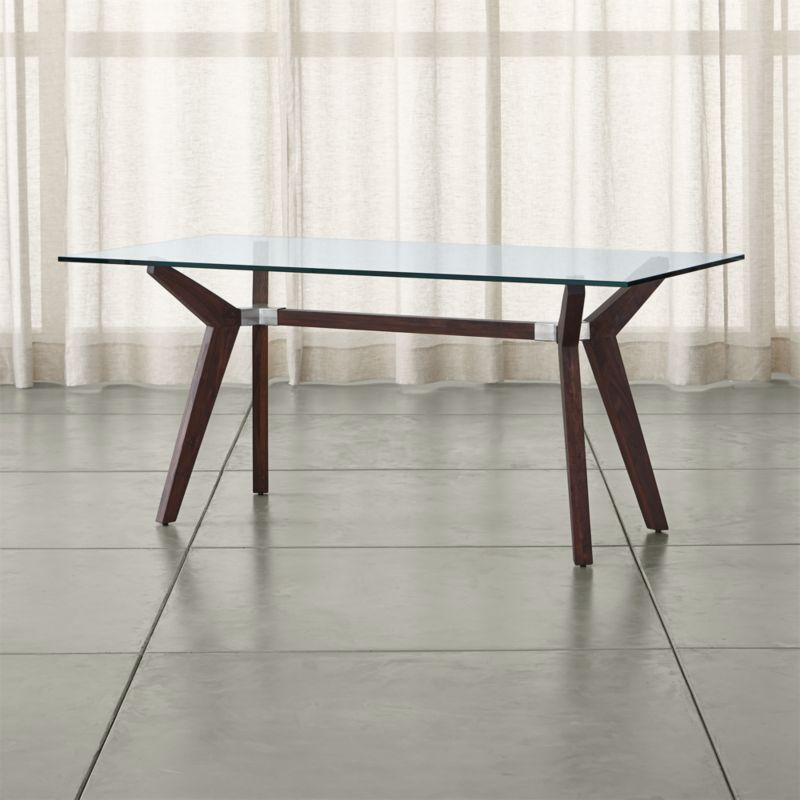"""The statement-making Strut work table offers clean, modern lines elegant enough for the dining room. A substantial glass top floats on dramatically-angled sheesham wood legs with a matte walnut stain. <NEWTAG/><ul><li>Sheesham wood with walnut stain, water based lacquer and wax topcoat</li><li>As with all solid woods, expansion and contraction may occur with seasonal changes in humidity</li><li>5/8"""" glass top</li><li>Steel joints</li><li>Seats six</li><li>Made in India and China</li></ul><br />"""