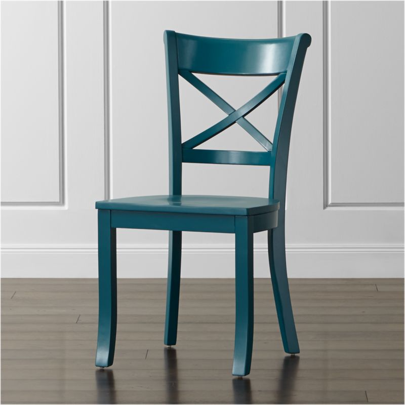 """A peacock blue painted finish adds colorful presence to our classic Vintner side chair, inspired by the substantial kitchen and dining chairs of farmhouses past. With sustainable solid wood construction featuring a contoured """"X"""" back and comfortable, carved seat, this is one inviting chair with vintage character. The Vintner Peacock Side Chair is a Crate and Barrel exclusive.<br /><br /><NEWTAG/><ul><li>Sustainable solid rubberwood</li><li>Peacock blue painted finish with clear lacquer topcoat</li><li>Made in Vietnam</li></ul><br />"""