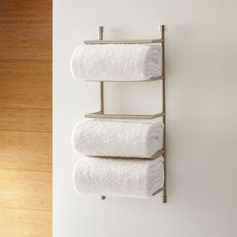 Brushed steel wall mount towel bar with 4 shelves holding white bath towels on a white bathroom wall