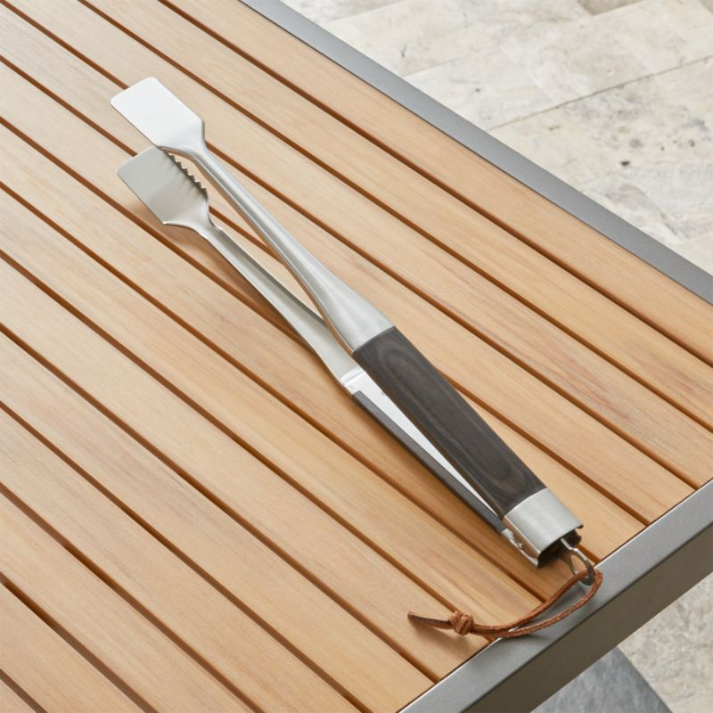 Smartly styled grilling essentials in sturdy stainless steel feature stay-cool black pakkawood handles with stainless steel tips and leather hanging loops. Serrated tongs with broad heads get a grasp on firm foods for easy turning and transferring. Long handles distance hands from heat source.<br /><br /><NEWTAG/><ul><li>Stainless steel head</li><li>Pakkawood handle</li><li>Stainless steel end with leather tie</li><li>Hand wash</li><li>Made in China</li></ul>