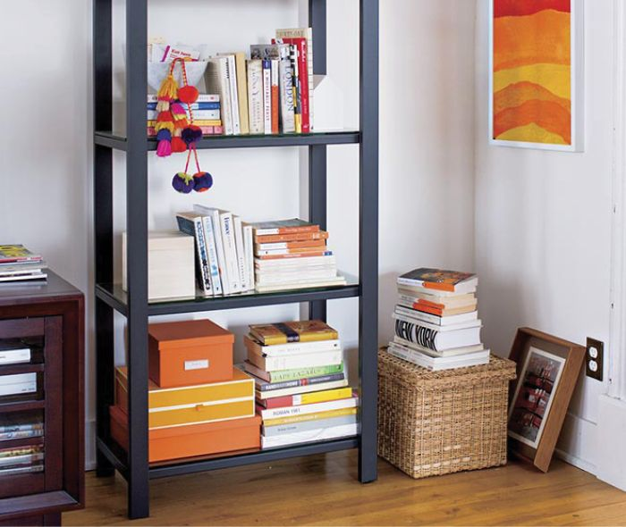 Black bookshelf with color coordinated books.