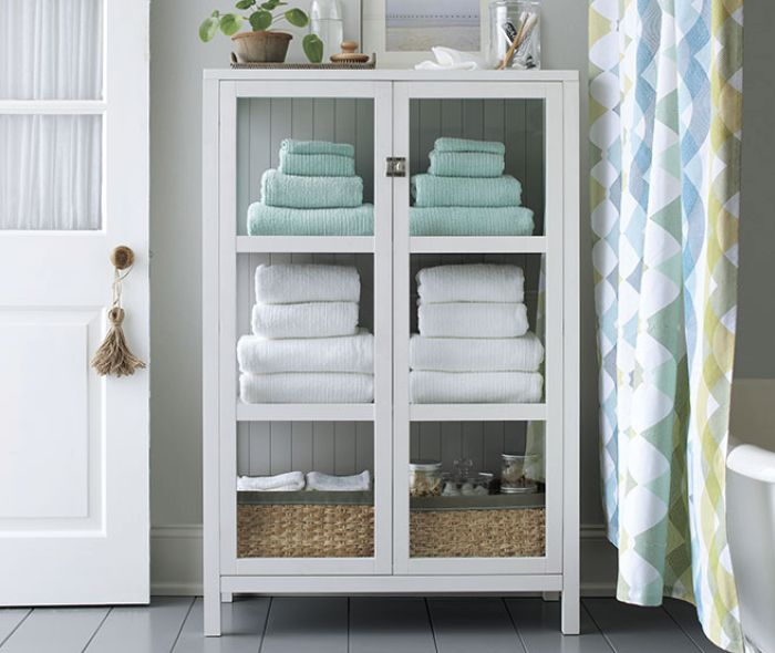 White storage cabinet with white and light blue towels.