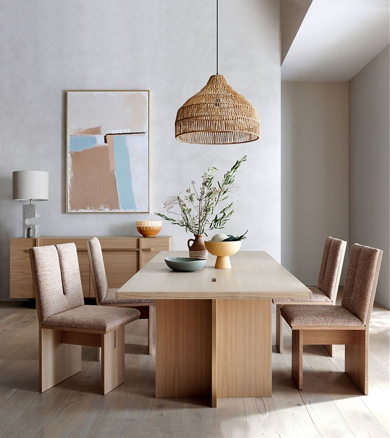 Dining room with natural wood table, four chairs, and rattan ceiling light; organic-looking decor and neutral colors