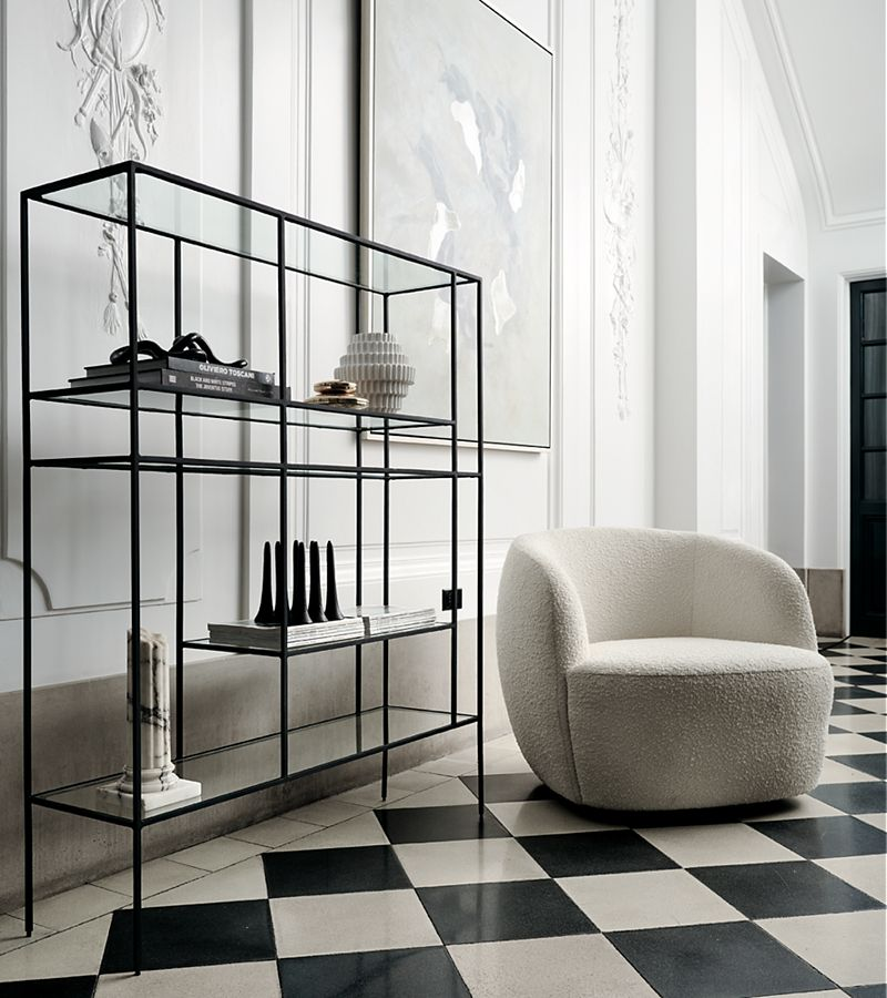 Room with plaster cast designs on the walls, checkered floor tiles and boucle swivel chair. Abstract art rests on minimalist shelf