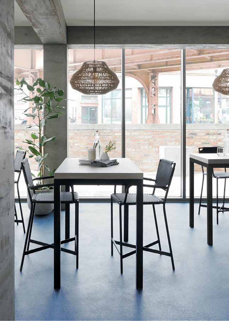 Modern cafe dining space featuring bistro tables and chairs, rattan pendant lights and a view of a bridge through the window