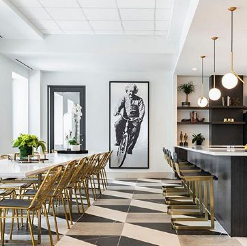 Modern art-deco inspired bar featuring black and brass details, a bold tiled floor and wall art of Einstein riding a bicycle