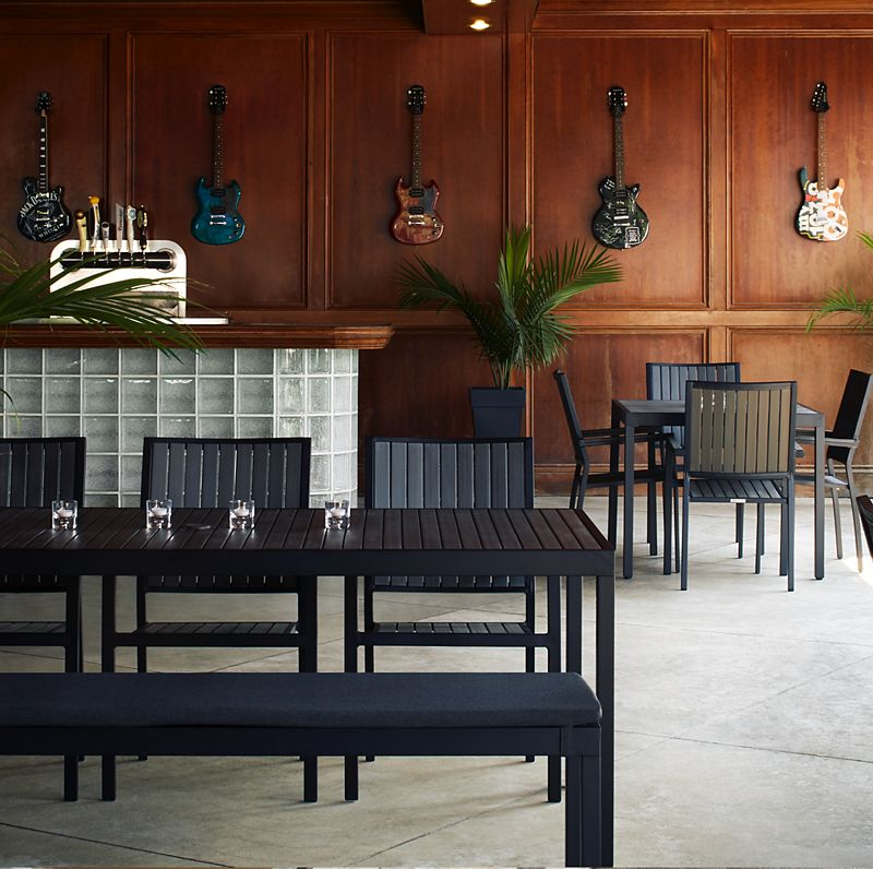 Dark bar space with with black wood furniture; walls covered with wood paneling and hanging guitar decorations