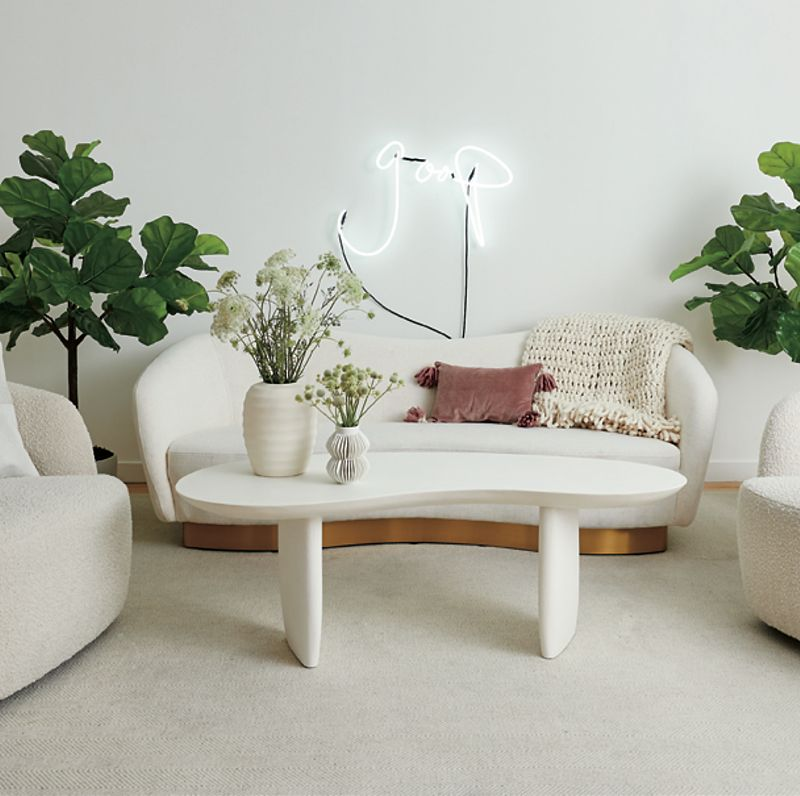 A white coffee table sits surrounded by a white couch and two white accent chairs, with a neon sign saying 'goop' hanging on the back wall