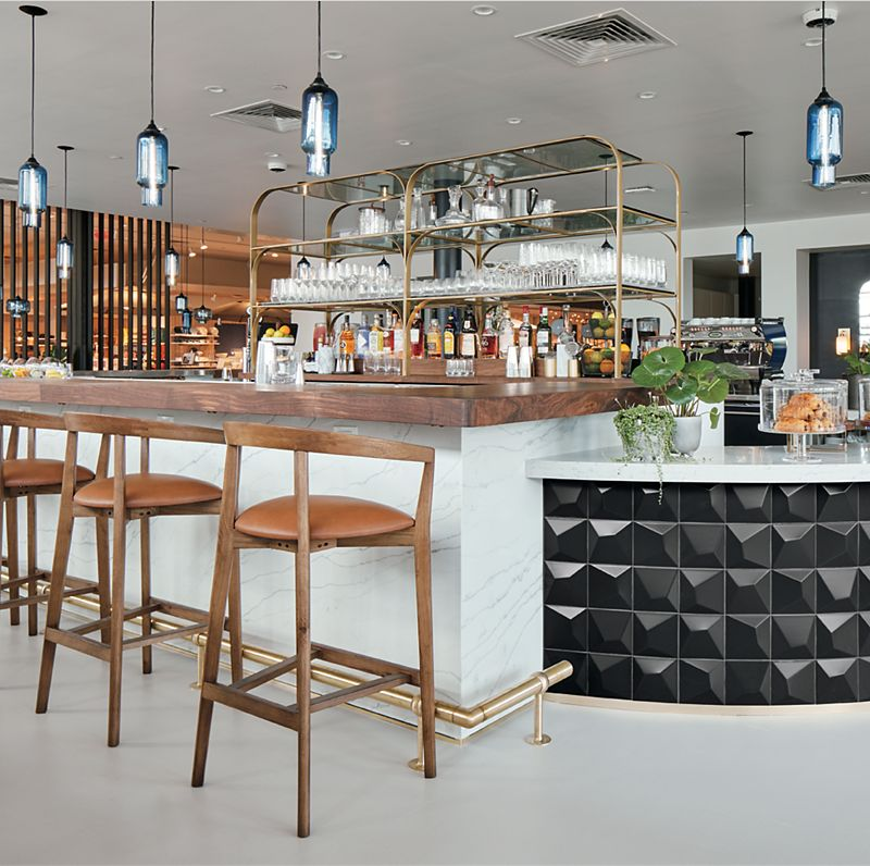 Bright bar space with liquor shelves in the background, wood bar stools  and metal pendant lights in the foreground