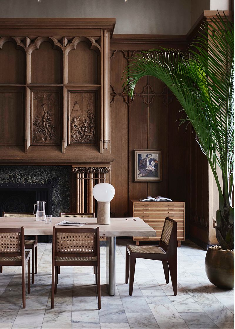 Dining space in a wood-paneled room; low cane chairs and long marble dining table in front of tall fireplace