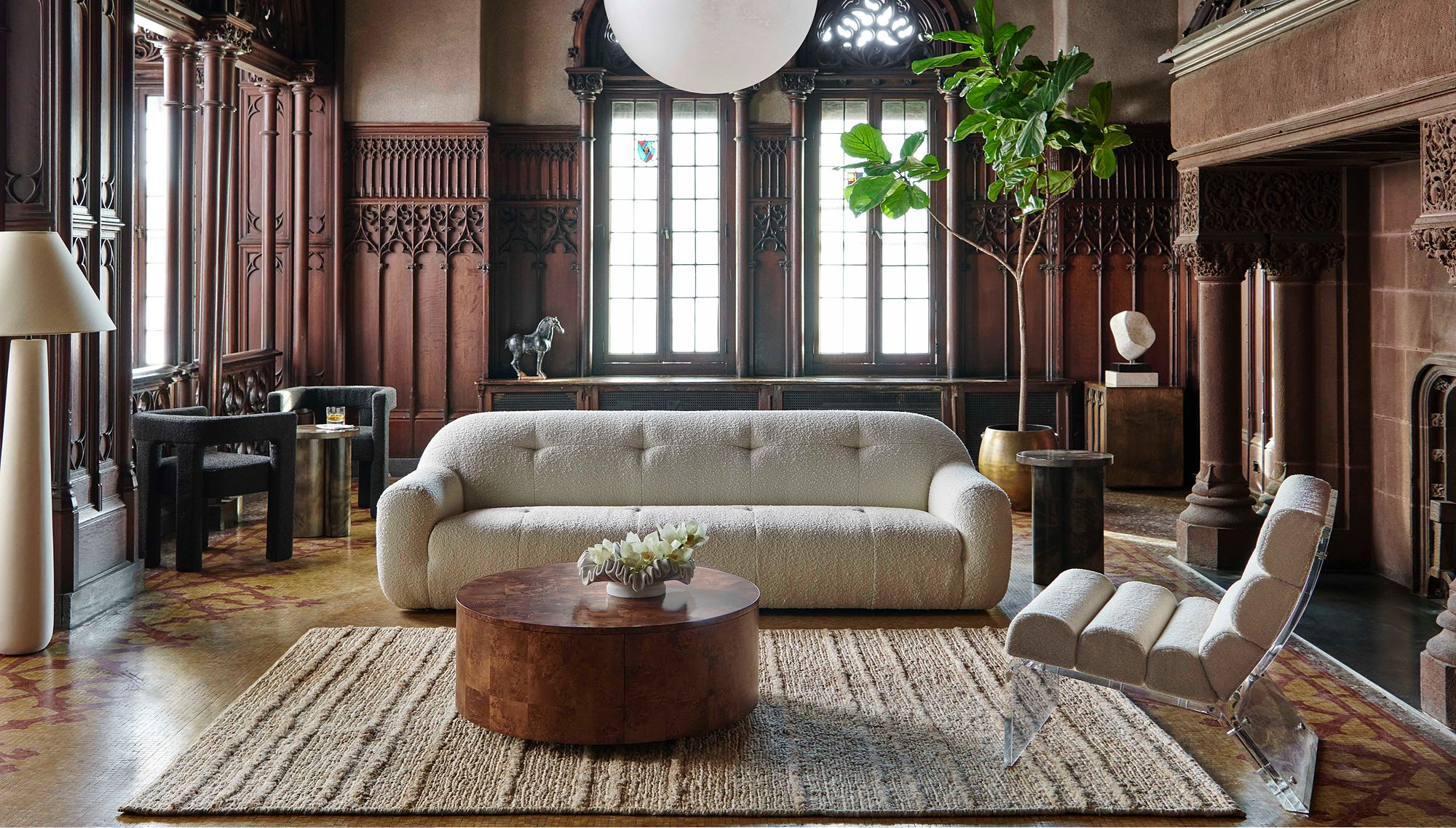 Textured sofa and round coffee table in a living room paneled with dark wood, plus gothic windows and a large fireplace