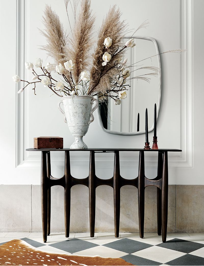 Thin brown console table holding a white vase with dried plants and two black candlesticks