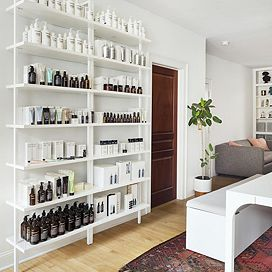 A large white shelf sits against a white wall, holding assorted bath products