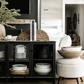 Black sideboard filled with assorted dishware and pots, with two bookends on top and a stool beside it