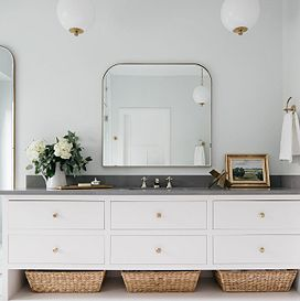 A grey bathroom counter sits on top of white drawer and brown woven baskets, with a large mirror on the center of the wall