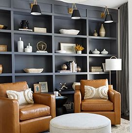 Tall black shelving sits against a wall holding various pieces of decor, and two brown leather arm chairs sit facing away from it