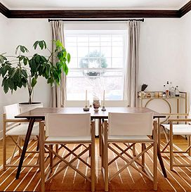 A brown table sits in the middle of a dining room, surrounded by six white and brown chairs