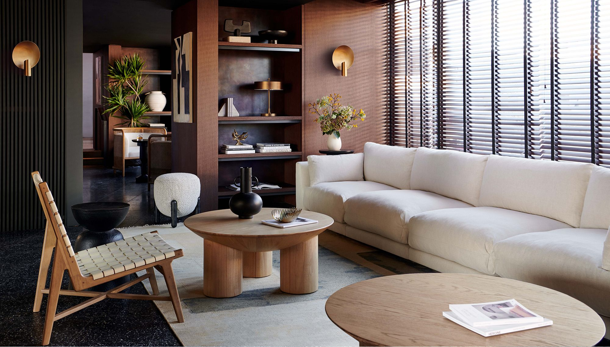 Room with long white couch and two circular wood accent tables