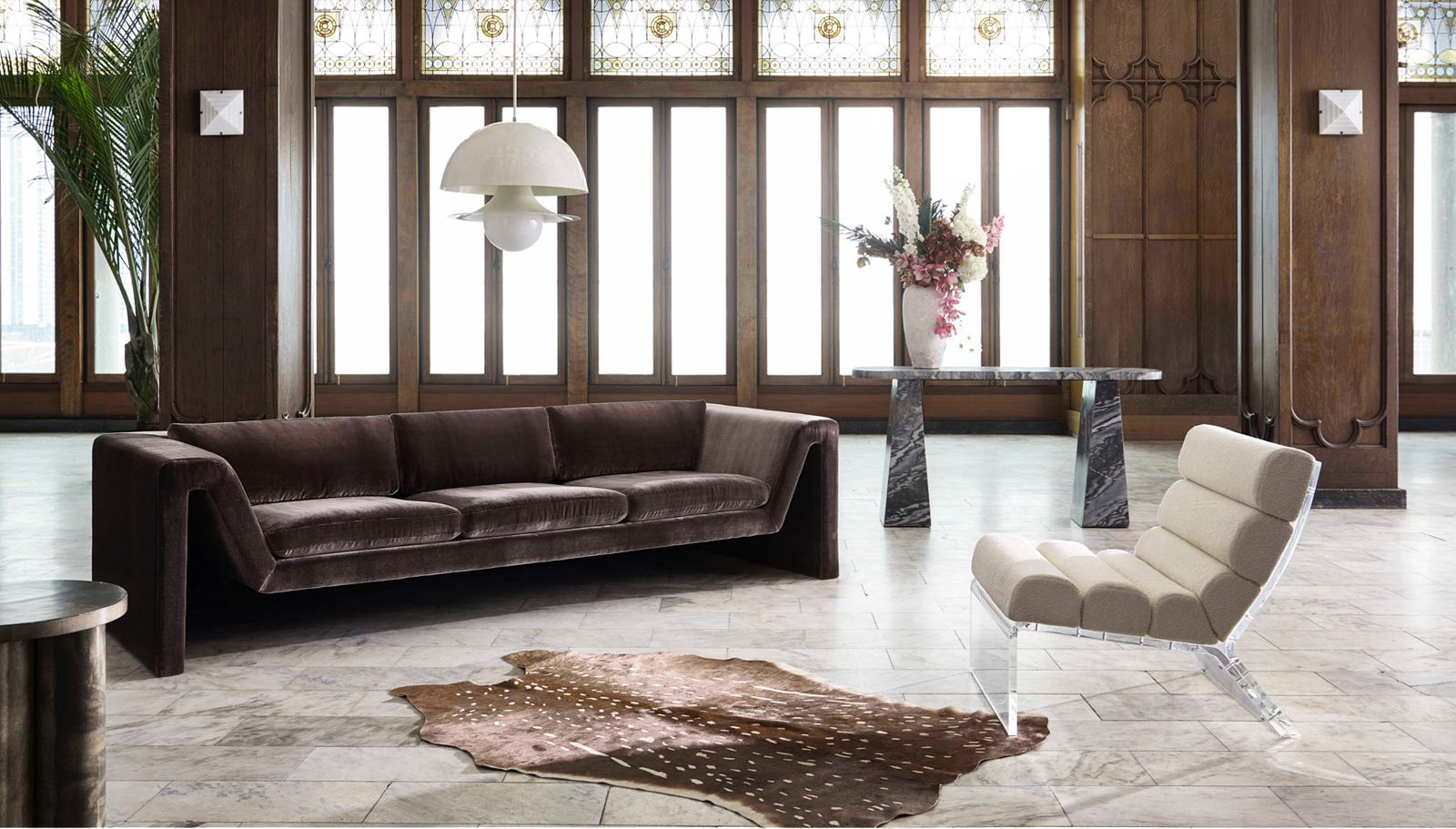 Large and spacious room with brown couch and white accent chair with a rug between them