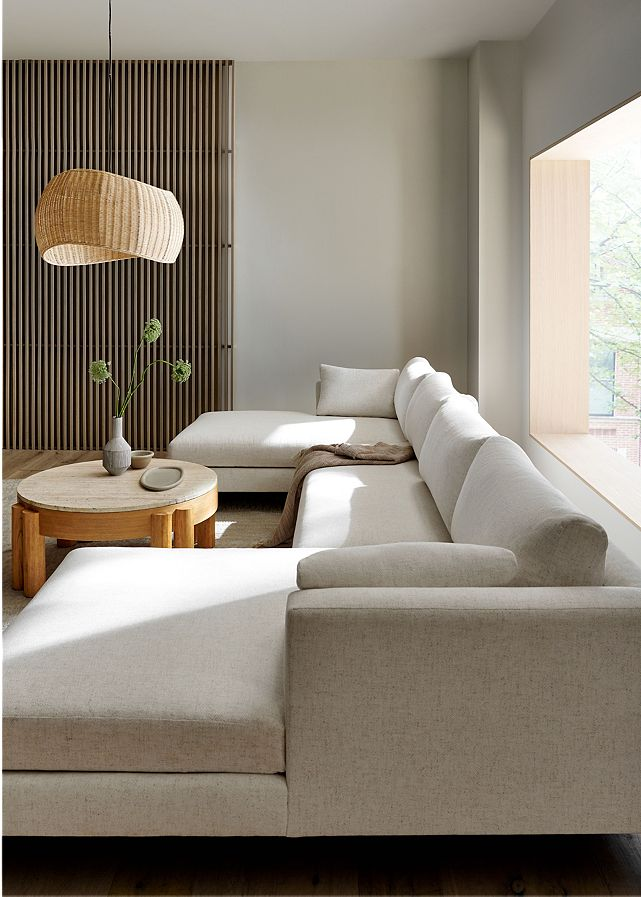 Living room with a long white sectional couch, round wood coffee table and a brown woven chandelier