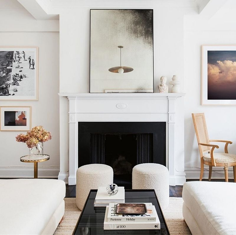 Living room with large fireplace and a piece of art on the mantel, with white upholstered seating and a black table