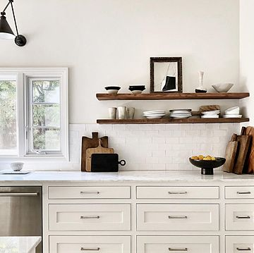 White marble kitchen counter with white drawers, and wooden shelves holding plates, bowls and cups