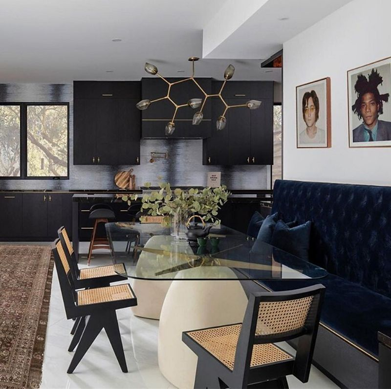 A joined dining room and kitchen space with a clear glass tabletop surrounded by a dark blue dining bench and brown and black dining chairs