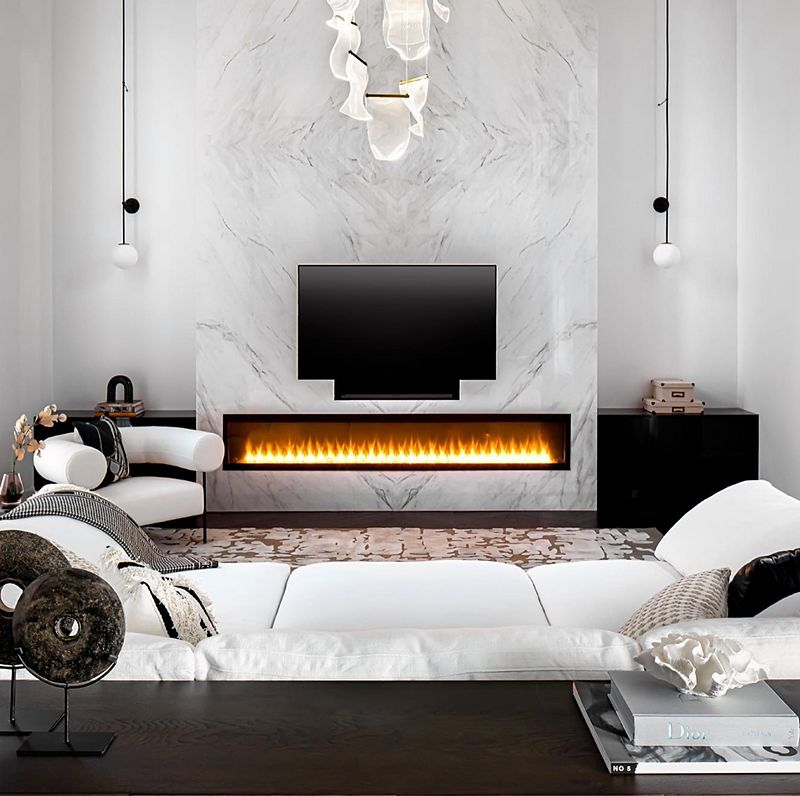 A modern living room with a wall fireplace, in front of which sits a wide white couch and curved white accent chair