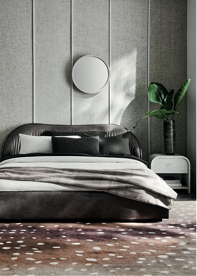 Bedroom with a low upholstered bed frame with white and grey bedding, next to which sits a white side table and plant in a black vase