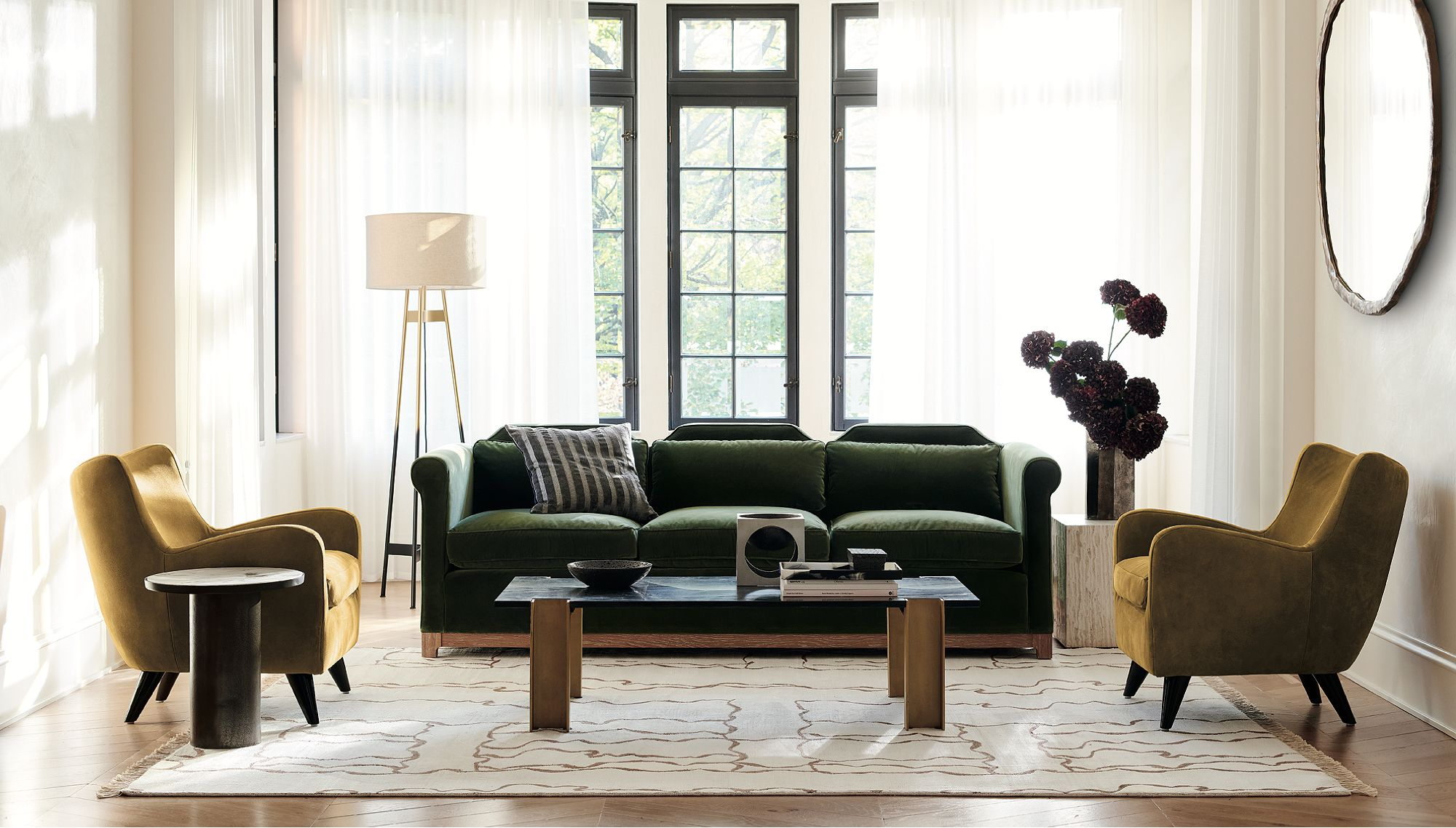 Living room with a dark green couch, two ochre accent chairs and a low coffee table in the center
