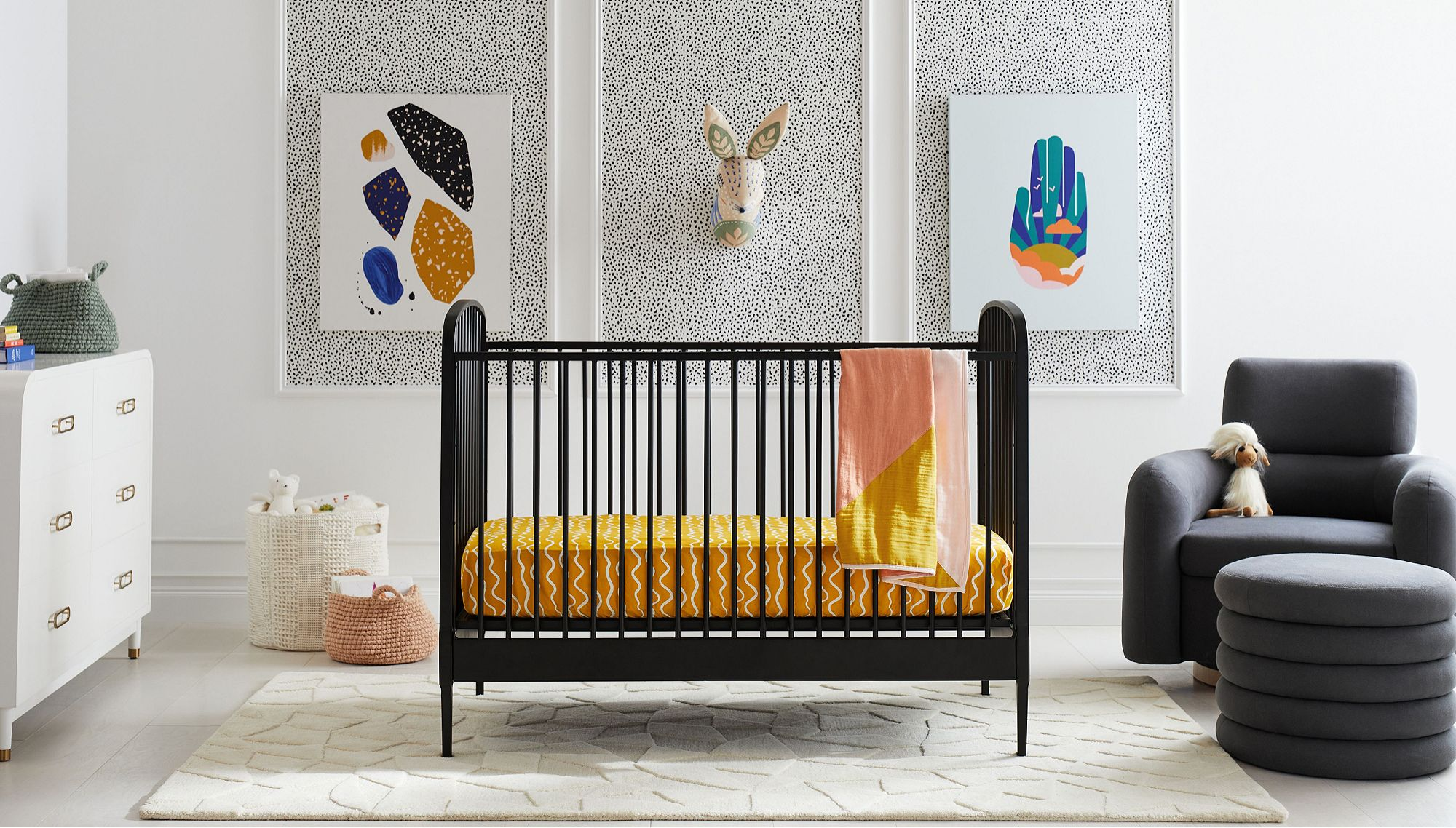 A nursery with a black crib with yellow bedding, surrounded by a white dresser, woven storage baskets and a dark grey chair