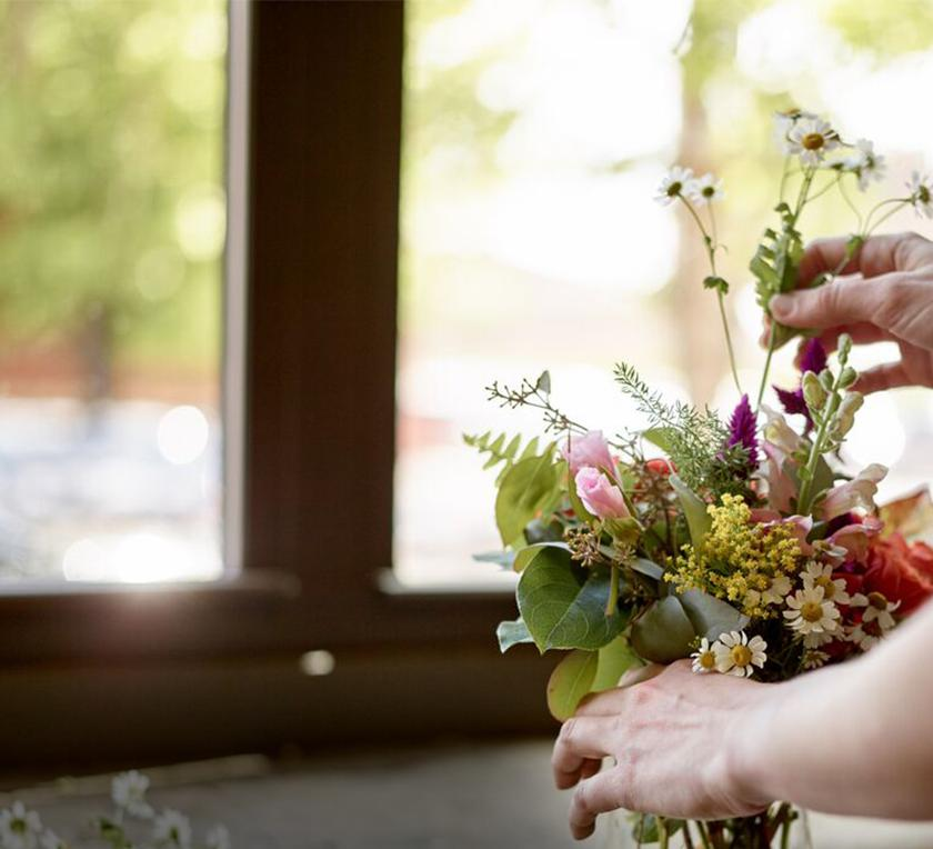a person adjusting flowers