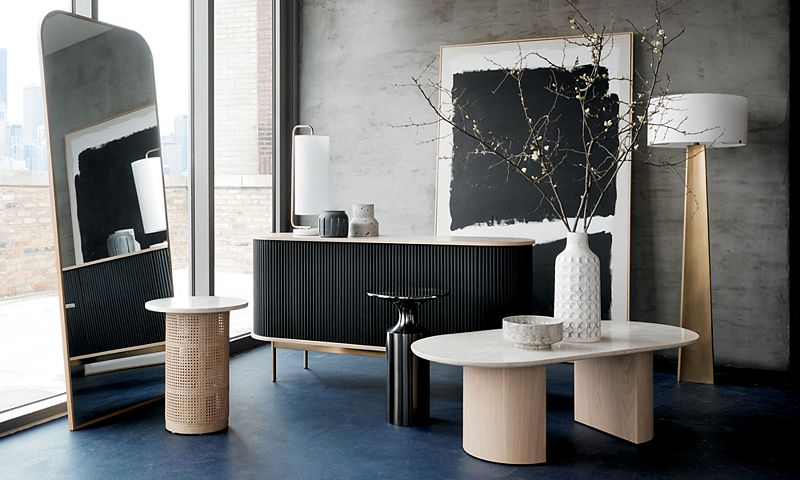 Black console table and light wood side table sit beside a standing mirror, with a large piece of art leaning against the back wall and a vase of dried branches in the foreground.