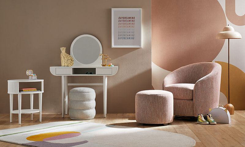 Blush-colored children's room with a light pink chair and round white mirror against the wall