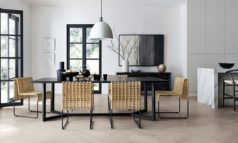 Spacious dining room with a black dining table, six brown chairs and a vase, fruit bowl and tea kettle on the table
