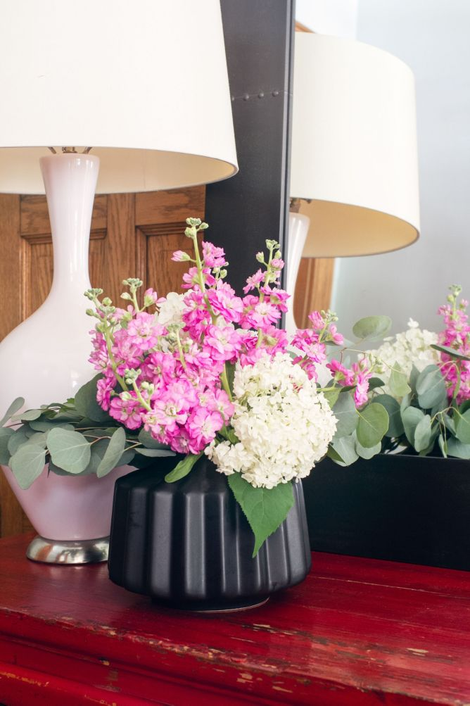 Flowers and lamp on entryway table