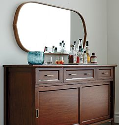 Large oval mirror with wood frame hanging on wall over wood sideboard with home bar on top