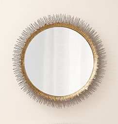 Round glass mirror framed by a gold and brass tinged sunburst